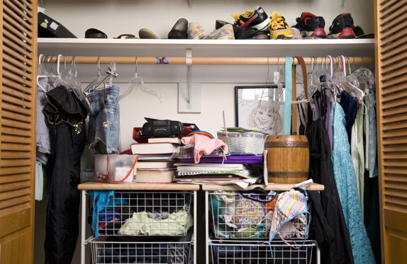Slide 1 of 14: Shoes and clothes in closet, close-up.