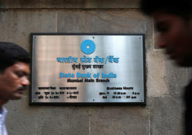 File: People walk in front of a signboard displayed at the head office of State Bank of India (SBI) in Mumbai February 14, 2014. SBI, the country's largest lender, on Friday posted a fourth straight consecutive drop in net income as an increase in bad loans clipped profitability.