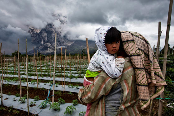 A woman carries her daughter in a nearby field as Mount Sinabung spews pyroclastic smoke on January 4, in Karo District, North Sumatra, Indonesia.