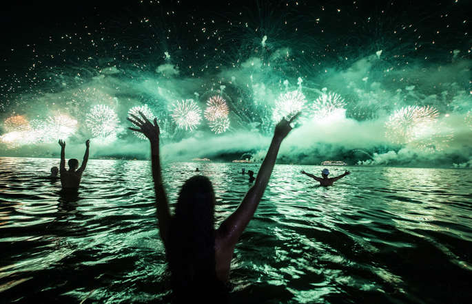 People cheer at the fireworks during the new year's celebration at Copacabana beach in Rio de Janeiro, Brazil, on January 1, 2014.