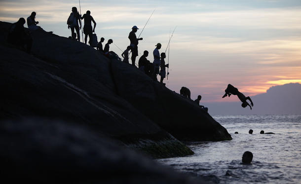 A man flips off the rocks at Arpoador at sunset during a summer heat wave in the city on January 3 in Rio de Janeiro, Brazil. Temperatures climbed to 104 in the city with a heat index measured at 122 degrees.