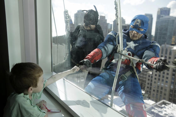 Window washers Pedro Castro, 45, dressed as Batman, and Roberto Duran, 32, as Captain America, right, entertain patient Zakk Carrier, 5, as they hang from the roof of the Ann & Robert H. Lurie Children's Hospital on April 15. This unusual form of entertainment for the young patients has become a beloved semi-annual tradition in Chicago.