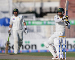 Pakistani batsman Mohammad Hafeez (right) hits a shot as team captain Misbah-ul-Haq looks on during the first day of the third and final Test match between Pakistan and New Zealand at the Sharjah cricket stadium in Sharjah on November 26, 2014.