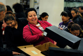 FILE - Imelda Diaz of Landover, MD checks to find her size for boots at a J.C. Penney store on Nov. 23, 2012.