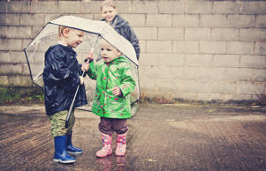 Two children share an umbrella.