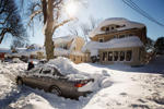A man digs out his snow-covered car in Buffalo, New York, November 21, 2014. Warm temperatures and rain were forecast for the weekend in the city of Buffalo and western New York, bringing the threat of widespread flooding to the region bound for days by deep snow. Areas where several feet of snow fell this week should brace for significant, widespread flooding, the National Weather Service warned on Friday.