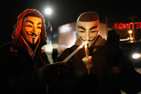 Protesters wearing Guy Fawkes masks take part in a candlelight vigil outside the Ferguson Police Department in Ferguson, Missouri, November 21, 2014.