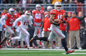 Ezekiel Elliott #15 of the Ohio State Buckeyes runs for a 65-yard touchdown rush in the first quarter against the Indiana Hoosiers at Ohio Stadium on November 22, 2014 in Columbus, Ohio.