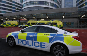 A Police car and ambulances are parked outside Queen Elizabeth hospital in Birmingham, UK