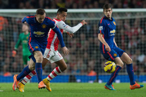 File: Manchester United's Wayne Rooney, left, competes for the ball with Arsenal's Alexis Sanchez during the English Premier League soccer match between Arsenal and Manchester United at the Emirates Stadium, London, Saturday, Nov. 22, 2014.