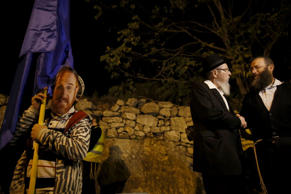 Jewish extremists gather on November 6, 2014 near the Old City of Jerusalem, where a Palestinian man recently tried to assassinate Rabbi Yehuda Glick (mask on the left).