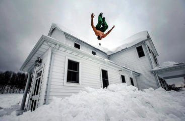 Phil Mohun does a back flip off of his family home after clearing snow from the roof following a massive snowstorm in Cowlesville, New York, November 22, 2014. Warm temperatures and rain were forecast for the weekend in the city of Buffalo and western New York, bringing the threat of widespread flooding to the region bound for days by deep snow.