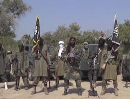 In this Friday Oct. 31, 2014 image taken from video by Nigeria's Boko Haram terrorist network, the leader of Nigeria's Islamic extremist group Boko Haram, center, has denied agreeing to any cease-fire with the government.
