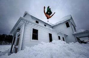 Phil Mohun does a back flip off of his family home after clearing snow from the roof following a massive snowstorm in Cowlesville, New York, Nov. 22, 2014.