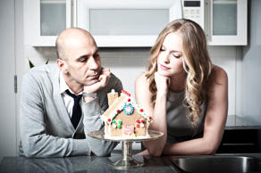 Couple in kitchen staring at a decorated gingerbread house.
