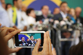 A reporter uses a smartphone to record video of Aecio Neves, a potential canidate for the president of Brazil.