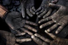 (For representation only) Workers display their coal-covered hands.