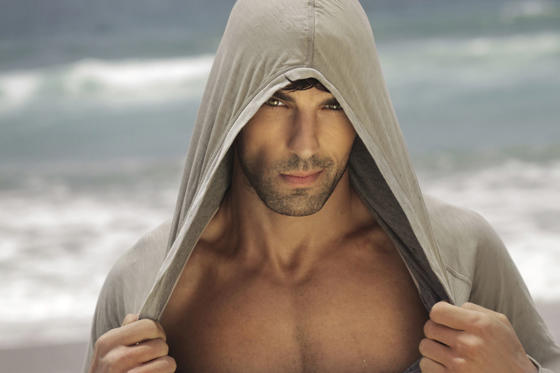 Sexy male model outdoors wearing a hooded shirt