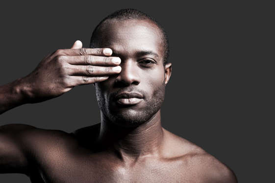 Portrait of young shirtless African man covering one eye with hand and looking at camera while standing against grey background