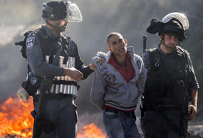 Israeli security forces detain an Arab-Israeli youth during clashes in the town of Kfar Kana, in northern Israel.