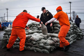 Erie County Holding Center inmates help pile sandbags to prepare for possible flooding following a massive snow storm in Williamsville, New York, November 23, 2014. Warm temperatures and rain were forecast for the weekend in the city of Buffalo and western New York, bringing the threat of widespread flooding to the region bound for days by deep snow.