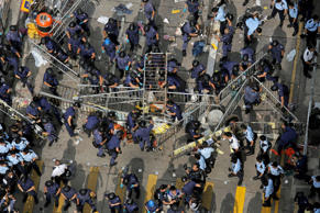Police officers clear a metal barricades while others tear down tents and canopies and carry away other obstructions after bailiffs issued a warning to the crowd that they would start enforcing the court-ordered clearance at an occupied area in Mong Kok district of Hong Kong Wednesday, Nov. 26, 2014. Hong Kong authorities cleared street barricades from the pro-democracy protest camp in the volatile Mong Kok district for a second day Wednesday after a night of clashes in which police arrested 116 people.