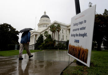 In this Sept. 25, 2014 file photo, pedestrian walks with an umbrella as the first rain of autumn falls in Sacramento, Calif. Much need precipitation in California is expected from a coming storm set to hit Nov. 30-Dec.1