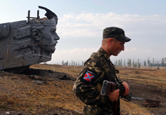 A Pro-Russian separatist stands near the damaged war memorial at Savur-Mohyla, a hill east of the city of Donetsk on August 28.