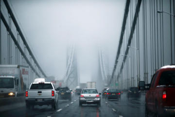 Cars make their way through the Washington bridge in New York November 26, 2014. A storm expected to blast the East Coast with rain and snow through Thursday morning is threatening to snarl traffic for millions and impede air travel ahead of the Thanksgiving holiday. The Thanksgiving holiday is one of the nation's busiest travel times with more than 46 million Americans expected to make trips between Wednesday and Sunday, travel group AAA said. REUTERS/Eduardo Munoz (UNITED STATES - Tags: TRANSPORT TRAVEL SOCIETY)