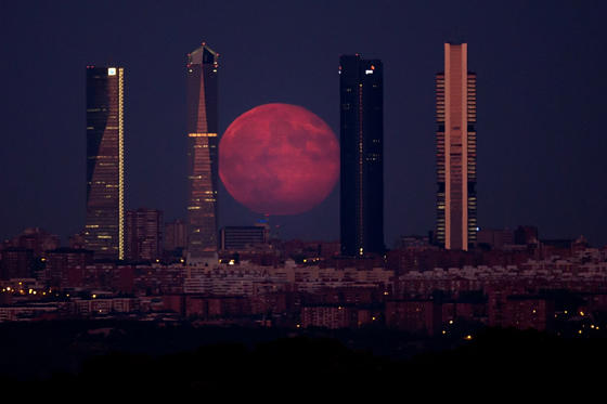 The second super-moon of the summer, which appeared 30 percent brighter and 14 percent bigger than normal, shines through the Four Towers Madrid skyscrapers on August 11, in Spain.