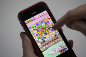 "A user plays the ""Candy Crush Saga"" puzzle game on an iPhone 5."