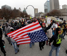 "Protesters march through downtown St. Louis, Wednesday, Nov. 26, 2014. Since a grand jury's decision was announced Monday night, Nov. 24, not to indict a white Ferguson, Mo., police officer who killed Michael Brown, an unarmed black teen, protesters in cities throughout the country have rallied behind the refrain ""hands up, don't shoot,"" and drawn attention to other police killings."
