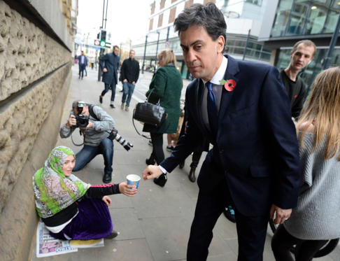 British Labour leader Ed Miliband donates money to a woman as he walks to a meeting with UK council leaders at the Town Hall on October 31, in Manchester, England.