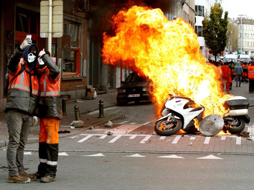 Protestors take a selfie in front of burning police motorbike in Brussels, on November 6. Belgians took to the street to protest the government's policies that will extend the pension age, contain wages and cut into public services.