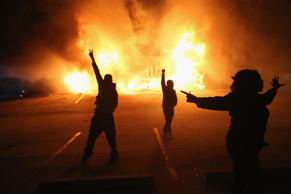 Demonstrators celebrate as a business burns after it was set on fire during rioting following the grand jury announcement in the Michael Brown case on November 24, 2014 in Ferguson, Missouri.