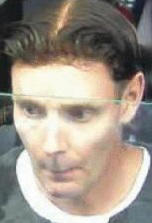 In this file crop of a Nov. 6, 2014 photo made from closed caption television footage and released by New Zealand Police, Phillip John Smith passes through Auckland Airport in Auckland, New Zealand.