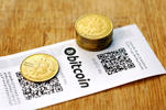 A Bitcoin (virtual currency) paper wallet with QR codes and coins are seen in an illustration picture taken at La Maison du Bitcoin in Paris July 11, 2014.