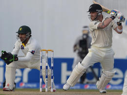 New Zealand captain Brendon McCullum (right) plays a shot as Pakistani wicketkeeper Sarfraz Ahmed looks on during the second day of the third and final Test match between at the Sharjah cricket stadium on November 28, 2014.