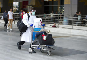 File: A traveller, who was not cleared after being screened for the Ebola virus on his arrival in India, walks towards an ambulance at the International airport in New Delhi