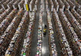 A worker gathers items for delivery from the warehouse floor at Amazon's distrib...