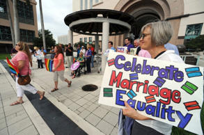 File photo of people gathered at the Palm Beach County courthouse to show support for gay marriage in Monroe County, in West Palm Beach, Fla.