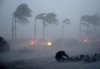 A man is blown down by typhoon Rammasun on July 18, 2014.  Typhoon Rammasun made landfall in Hainan Island and packed winds of up to 216 km per hour.