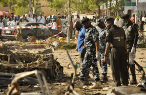 File: Bomb detection security personnel inspect the wreckage of a car believed to be used in the Kano Central Mosque bombing, November 28, 2014.