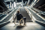 Businessman on a wheelchair against modern stairs.