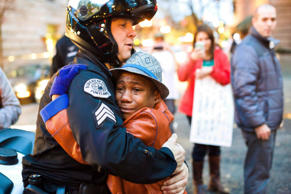 In this photo provided by Johnny Nguyen, Portland police Sgt. Bret Barnum (left) consoles 12-year-old Devonte Hart at a rally in Portland, Oregon, where people gathered in support of the Ferguson protests.