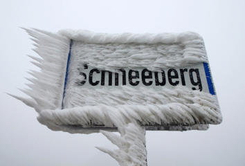 A sign board for the village of Schneeberg, translated as Snow Mountain, is covered with ice, in northern Austria.