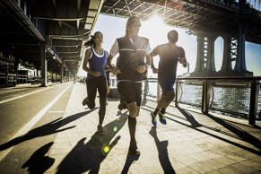 Team running together on bridge, New York, USA