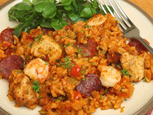 Slide 18 of 51: LOUISIANA: Sit down with a steaming hot plate of jambalaya, made with rice, chicken, sausage, vegetables, and sometimes seafood.