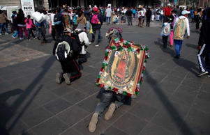 A man crawls on his knees, carrying an image of the Virgin of Guadalupe on his back, as he approaches the entrance to the Basilica of Guadalupe in Mexico City, Thursday, Dec. 11, 2014.
