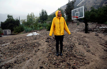 Homeowner Amanda Heinlein stands on a mud landslide covering a basketball court near her house in Azusa, Calif., Friday, Dec. 12, 2014.